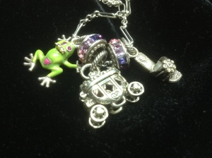We got this for my Momma!  There is my Daddy as the Frog Prince!  He has a pink heart on his hinny 'cause my Momma likes pink!  That is her fairy princess carriage.  Daddy says all fairy princesses has one.  That is my Momma's shoes that my Daddy found and took back to her!